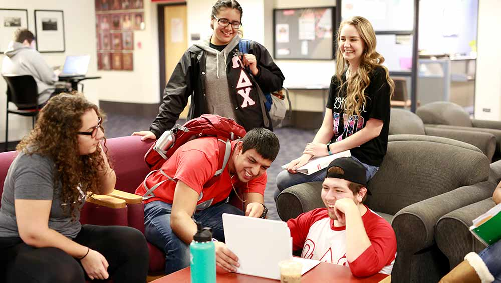 students laughing looking at a laptop