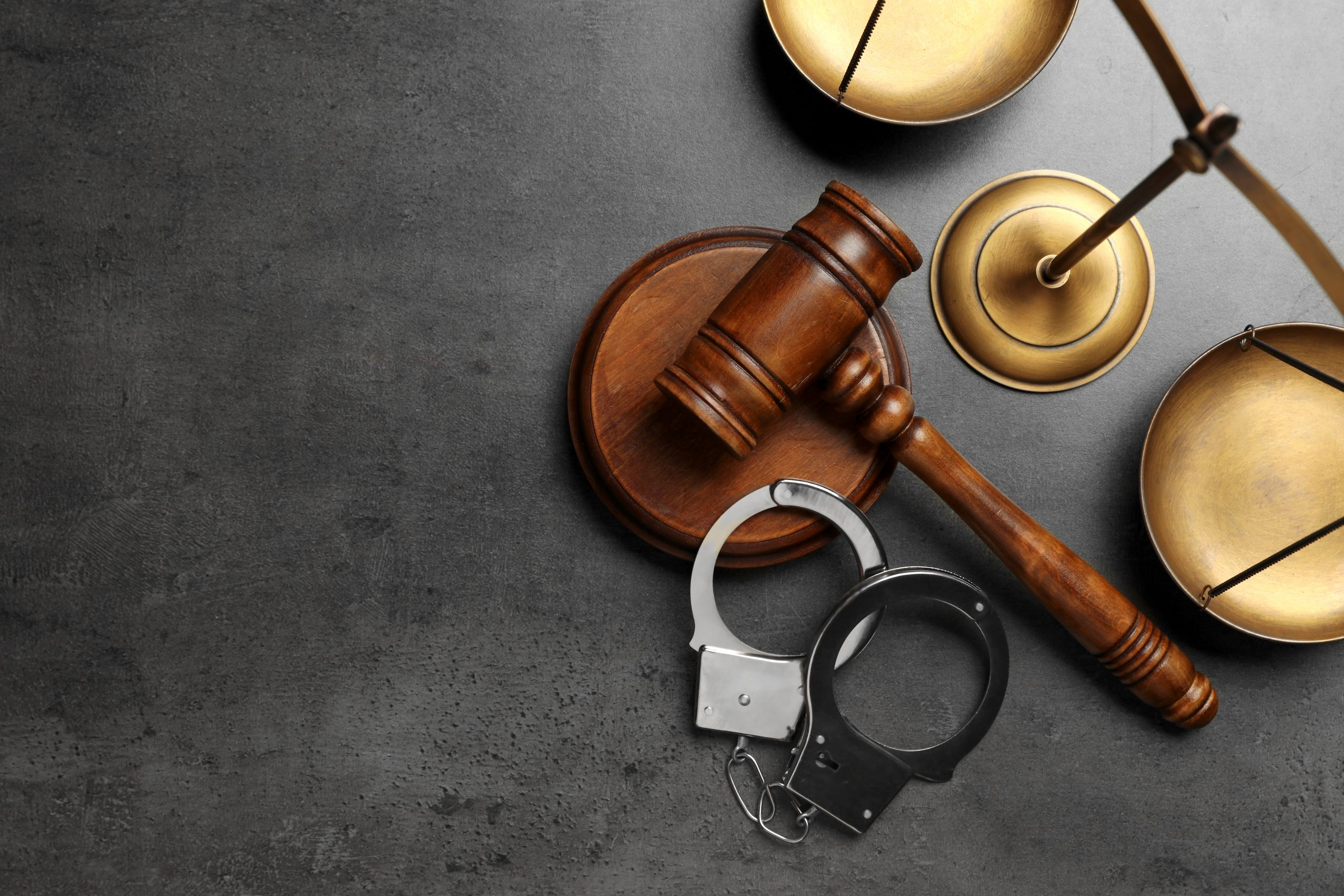 Handcuffs, judge gavel, and scale.