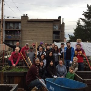 Group of volunteers working outside in a garden, posing for the picture holding a variety of garden tools