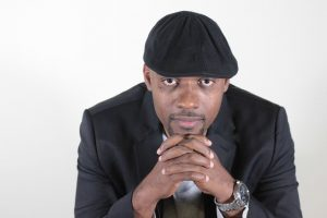 Africian American man, Lasana Omar Hotep, sitting with his hands clutched under his chin looking at the camera wearing a black hat and black suit blazer