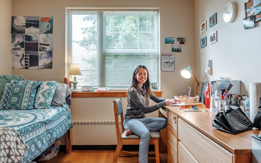 Person sitting in a chair in a residence hall room with photos on the wall