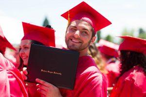 Grad smiling and holding degree folder