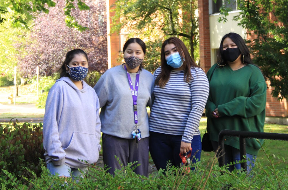 Students smiling outside of the dorms wearing masks