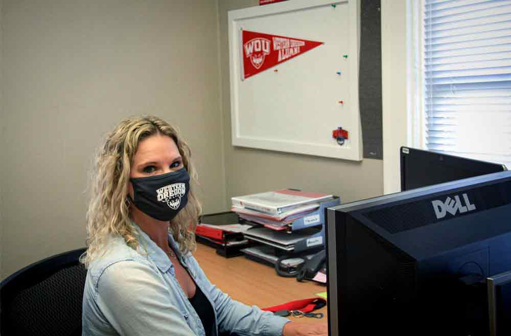 WOU employee wearing a mask at her desk
