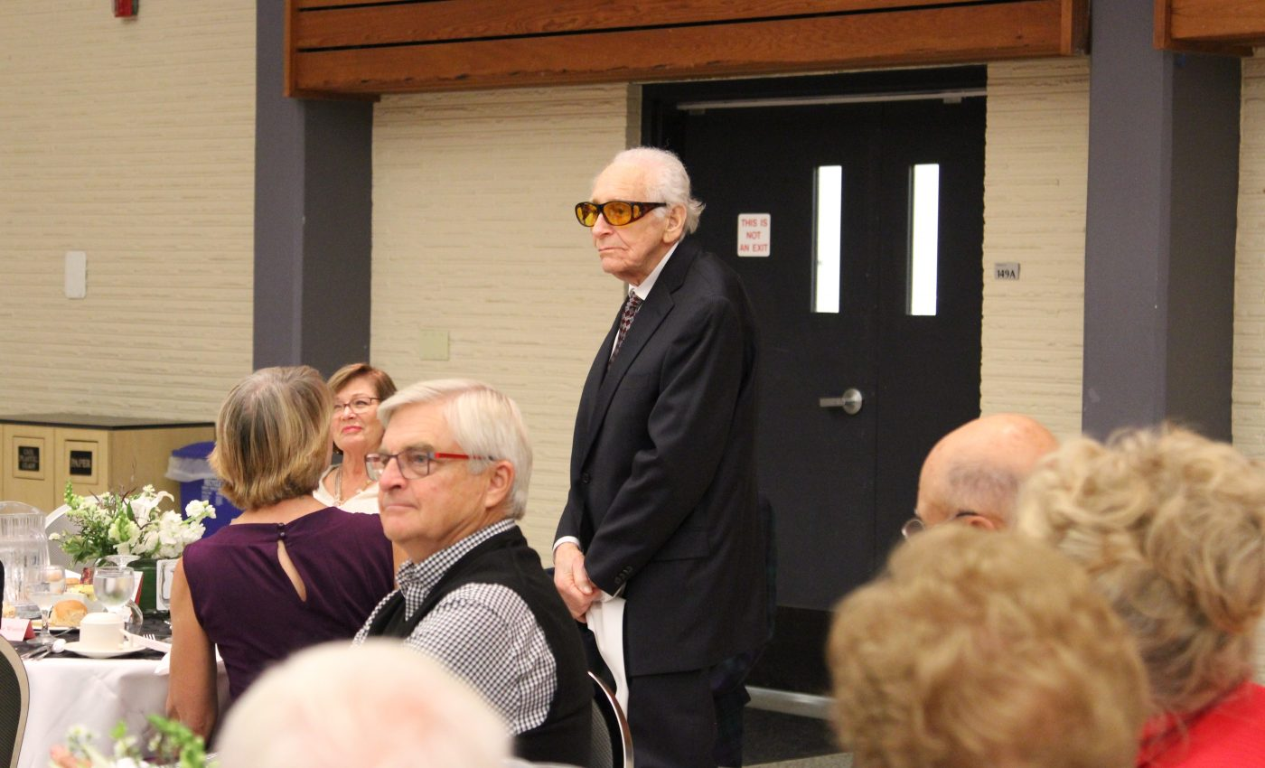 old man with glasses standing near seated individuals