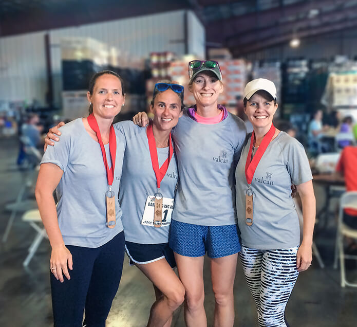 a group of people in running clothes standing in a winery warehouse