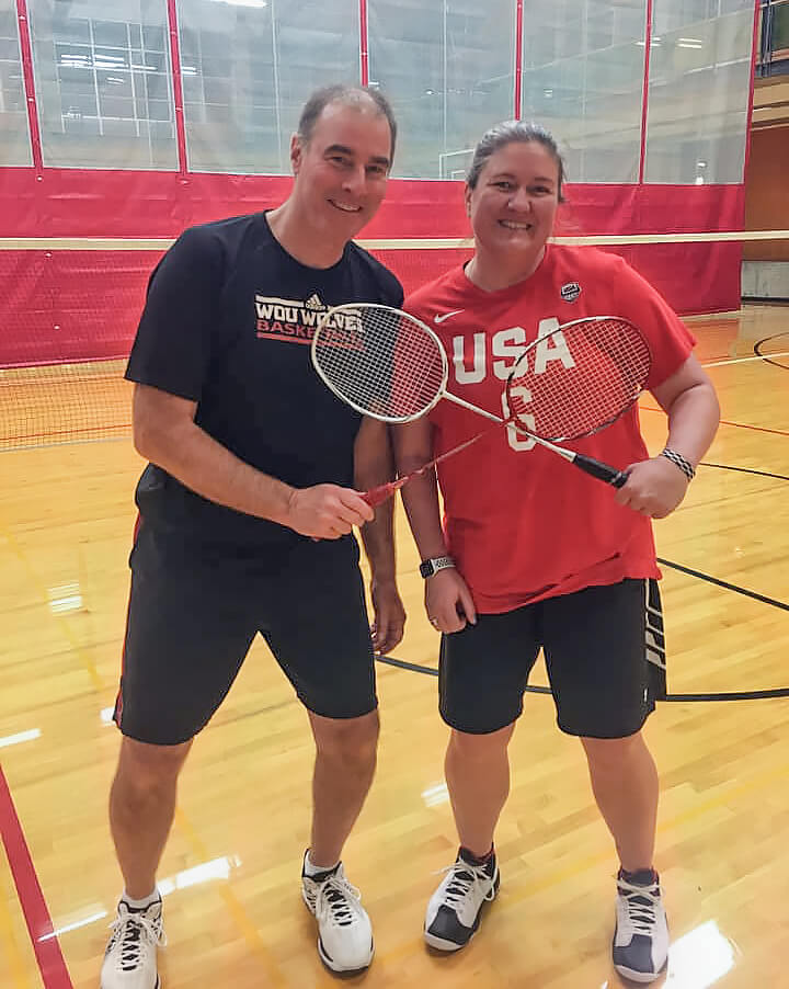 two people in a gym holding racquets