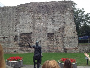 A statue of Emperor Trajan in front of the portion of the London Wall at the Tower of London.